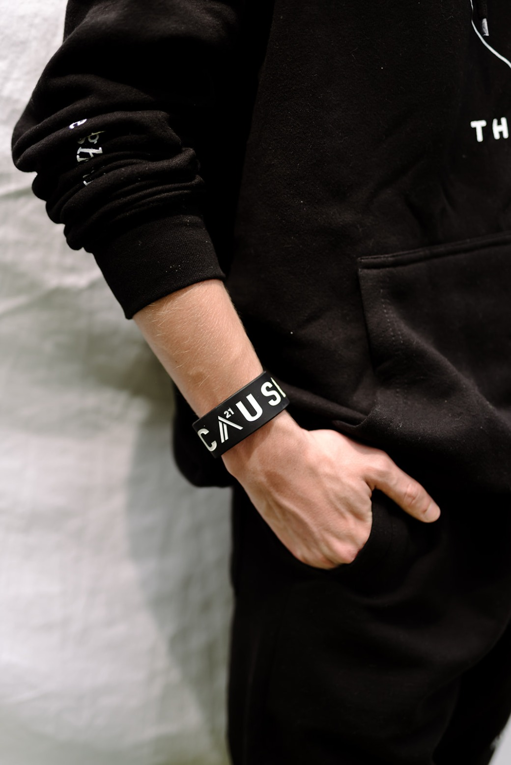 Black thick Because Band on arm with hand in pocket