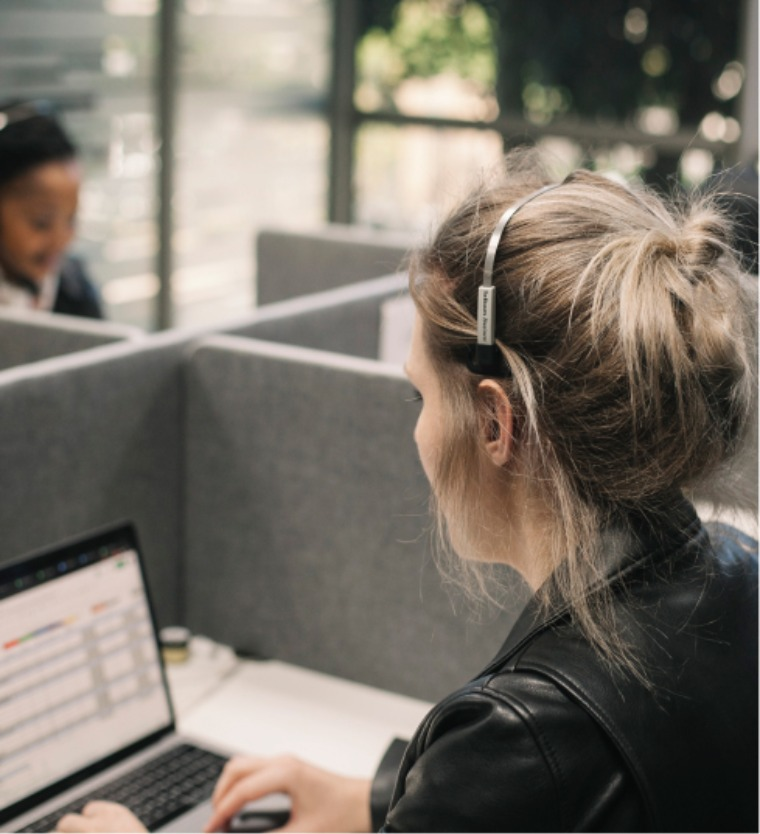 Blonde woman working the human trafficking hotline in South Africa. Wearing headset and on computer.
