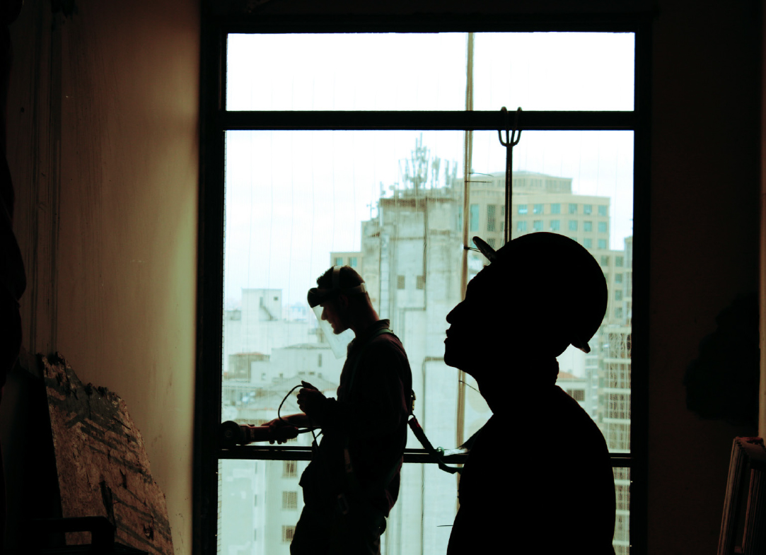 construction workers inside of a building, infront of window