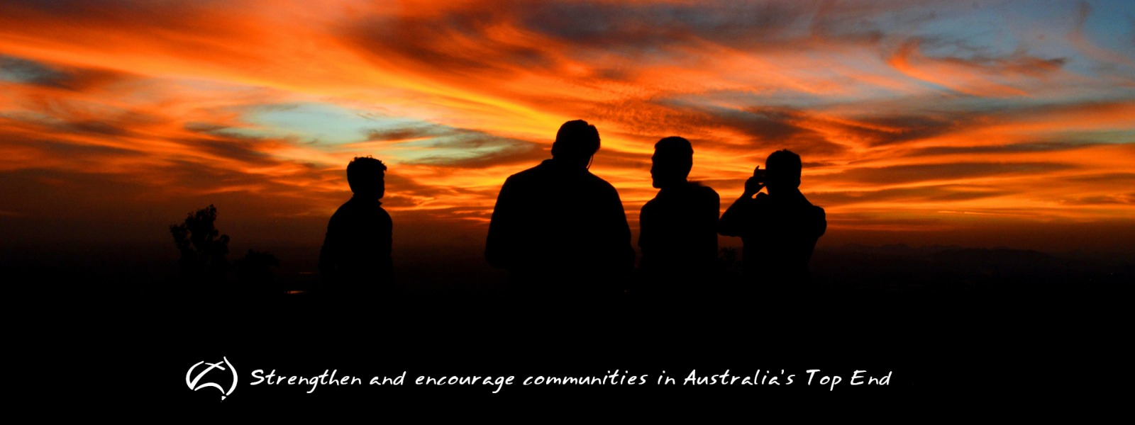 People silhouetted in front of a a sunset with a white BCA logo and text: Strengthen and encourage communities in Australia's Top End